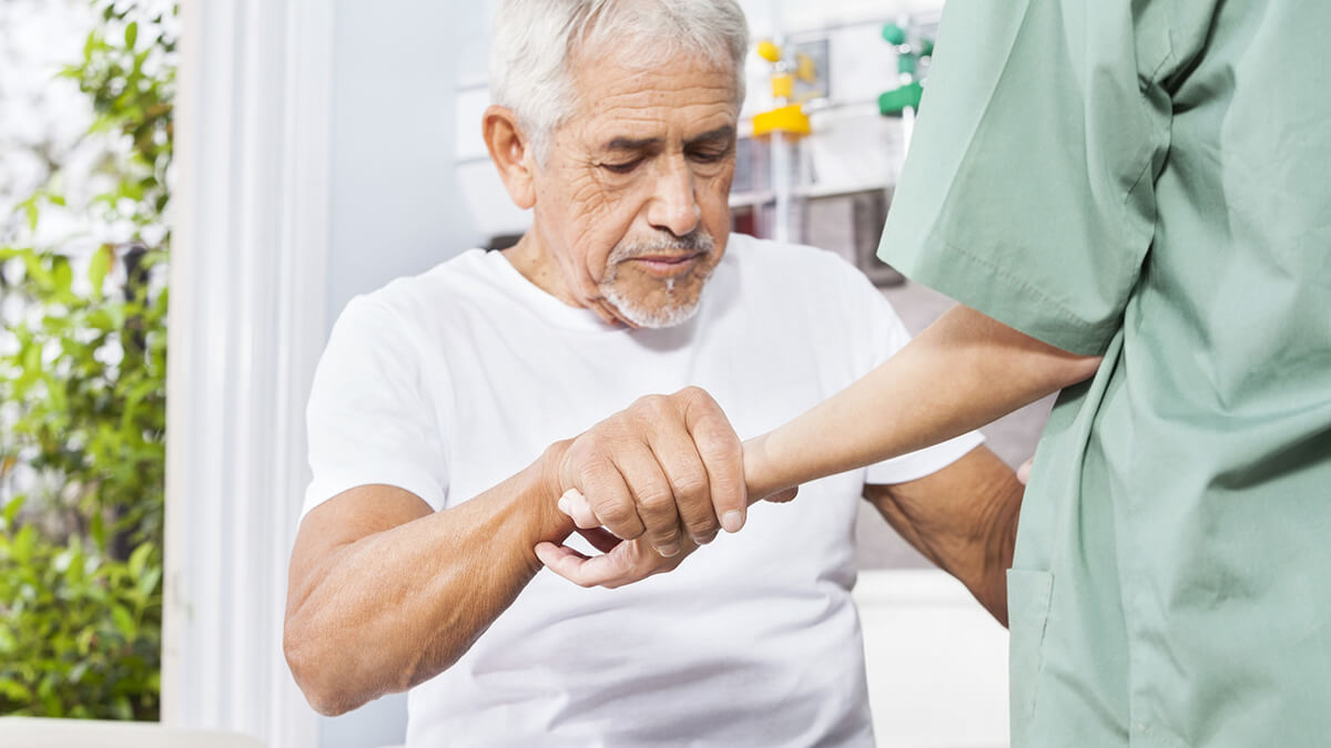 elderly man being helped in a long term care facility
