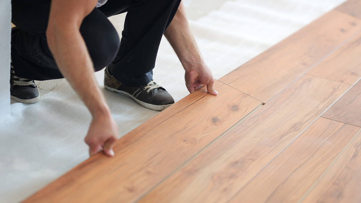 person installing hardwood flooring for home sale